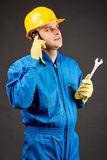 Young constuction worker speaking on phone and holding a wrench Royalty Free Stock Photo