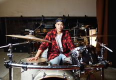 Drummer. Young contemporary drummer sitting in studio or garage in front of drum set Stock Photos