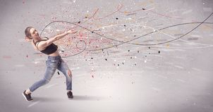 Urban dancing with lines and splatter. A young contemporary energetic dancer in action in front of a grey wall background with lines, spray dots and splatter Stock Photography