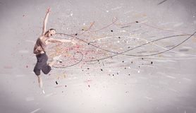 Urban dancing with lines and splatter. A young contemporary energetic dancer in action in front of a grey wall background with lines, spray dots and splatter Stock Images