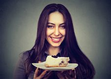 Excited woman having cheesecake slice. Young content brunette smiling at camera holding plate with cheesecake slab Stock Photography