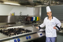 Young content chef standing next to hotplate Royalty Free Stock Image