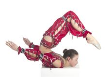 A young contortionist,circus performer in a red suit. Acrobat does gymnastic exercises , the isolated image on a white background. Young athletic woman in a red Royalty Free Stock Images