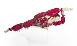 A young contortionist,circus performer in a red suit. Acrobat does gymnastic exercises , the isolated image on a white background. Young athletic woman in a red Royalty Free Stock Photo
