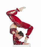 A young contortionist,circus performer in a red suit. Acrobat does gymnastic exercises , the isolated image on a white background. Young athletic woman in a red Royalty Free Stock Photos
