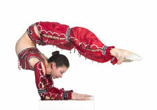 A young contortionist,circus performer in a red suit. Acrobat does gymnastic exercises , the isolated image on a white background. Young athletic woman in a red Stock Photos
