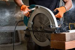 Close-up of carpenter using electric circular saw to cut wood planks. A young contractor cuts wooden planks in a carpentry workshop using an electric buzz saw royalty free stock photography