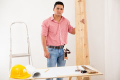 Young contractor at work at a house. Good-looking contractor carrying some wood and remodeling a house Royalty Free Stock Photo