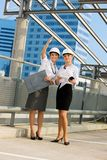 Young contractors. Young female contractors in a front of building site royalty free stock photo