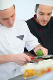 Young cook apprentice with chef supervising Stock Images