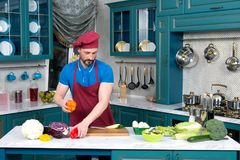 Young Cook in apron and cap takes red and yellow paprika. Man cooking salad at kitchen. Guy put vegetables for salad on cutting board for preparation of dinner Stock Image