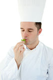 Young cook with closed eyes tasting a herb Stock Photo
