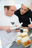 Young cook with cooking chef preparing dessert Royalty Free Stock Images