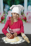 Young cook cuts out dough circle Royalty Free Stock Photos