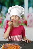 Young cook enjoys smell of sausage Royalty Free Stock Photos