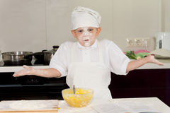 Young cook with a face full of flour shrugging Stock Photography