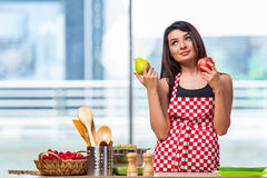 The young cook with fruits in the kitchen Royalty Free Stock Photos