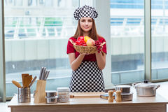The young cook with fruits in the kitchen Stock Images