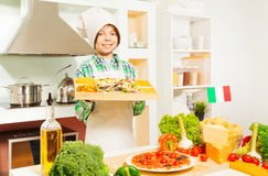 Young cook holding tray with mix of Italian pasta Stock Image