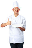 Young cook keeps an empty plate with thumb up. Isolated over white Stock Photography