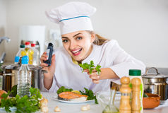 Young cook with prepared salmon in professional kitchen Royalty Free Stock Photo