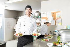 Young Cook Smiling While Presenting Dish In Kitchen. Confident chef showing plates of chicken meat with vegetables in kitchen stock image