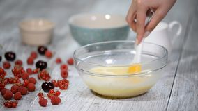 Young cook stirs cream in bowl.