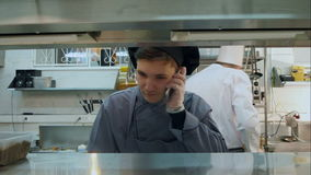 Young cook trainee talking on the phone in the professional kitchen stock footage