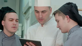 Young cook trainees having discussion with chef holding tablet stock video footage