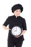 Young cook woman in black uniform with clock isolated on white Royalty Free Stock Photo