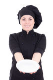 Young cook woman in black uniform with empty plate isolated on w Royalty Free Stock Photos