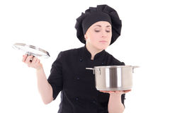 Young cook woman in black uniform holding pan isolated on white Royalty Free Stock Images