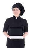 Young cook woman in black uniform showing laptop with copypaste Stock Photos