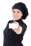 Young cook woman in black uniform showing visiting card isolated Stock Photos