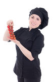 Young cook woman in black uniform with tomato isolated on white. Background Royalty Free Stock Image