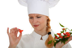 Young cook woman trying to eat chilli Stock Photo