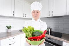Young cook woman in uniform with vegetarian food in modern kitch Royalty Free Stock Photos