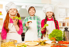 Young cooks holding ingredients for hamburgers Royalty Free Stock Image