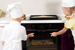 Young cooks placing their pizzas in the oven Royalty Free Stock Image