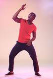 The young cool black man is dancing. The young cool black man in a red shirt is dancing in studio pink light Stock Photos