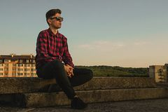 A young cool guy in hipsters shirt and sunglasses on the roof with blue sky and clouds. A young cool guy in hipsters shirt and sunglasses sitting on the roof stock photos