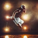 Young man break dancer. Young cool man break dancer jumping in club with lights and smoke. Tattoo on body Royalty Free Stock Images