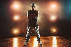 Young man break dancer. Young cool man break dancer standing in club with lights and smoke. Tattoo on body Royalty Free Stock Photo