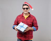 Young cool man with Santa Claus hat and gift Royalty Free Stock Image