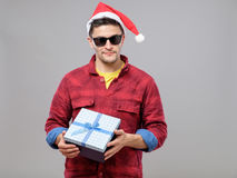 Young cool man with Santa Claus hat and gift. Young cool hipster man with Santa Claus hat, gift and sunglasses isolated Royalty Free Stock Photography