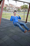 Young cool man sitting on a swing Royalty Free Stock Images