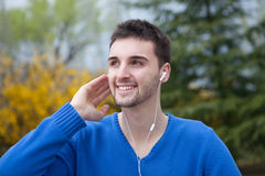Young cool men in the park listening music with earphones Royalty Free Stock Image