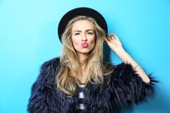 Young cool woman in fur and hat on  background. Young cool woman in fur and hat on blue background Stock Image