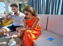 Young copule having coffee in lounge bar. Outdoor Royalty Free Stock Images