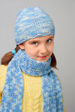 Young Coquette. Smiling girl with the braids, dressed in knitted pullover, scarf and hat stock image